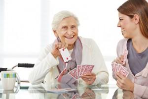 Junge Frau spielt mit einer glücklichen Seniorin im Seniorenheim Karten