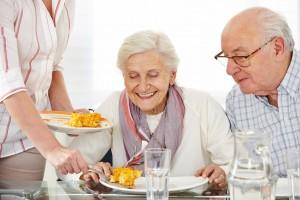 Zwei lächelnde Senioren essen Lunch im Pflegeheim